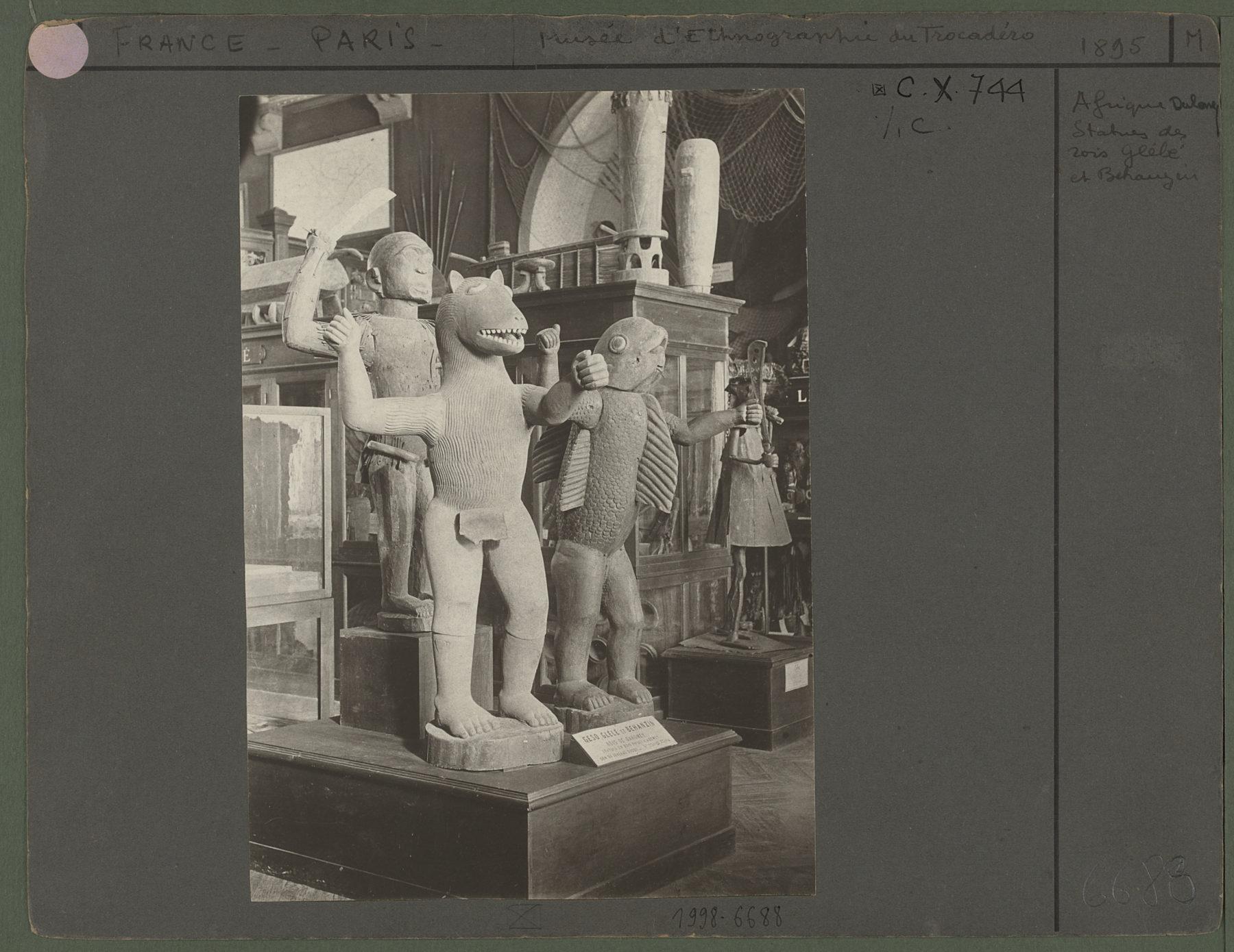 Statues des rois Glélé et Béhanzin Photographe : Société d'excursions des amateurs de photographies (1887 - 1938). Vue des rois Glélé et Béhanzin dans les salles du musée d'ethnographie du Trocadéro. On aperçoit également la sculpture dédiée à Gou (71.1894.32.1). Elles sont aujourd'hui conservées au musée du quai Branly. Béhanzin (1844-1906), roi du Dahomey. Glélé, roi du Dahomey de 1858 à 1889). PP0001264 Anonyme
