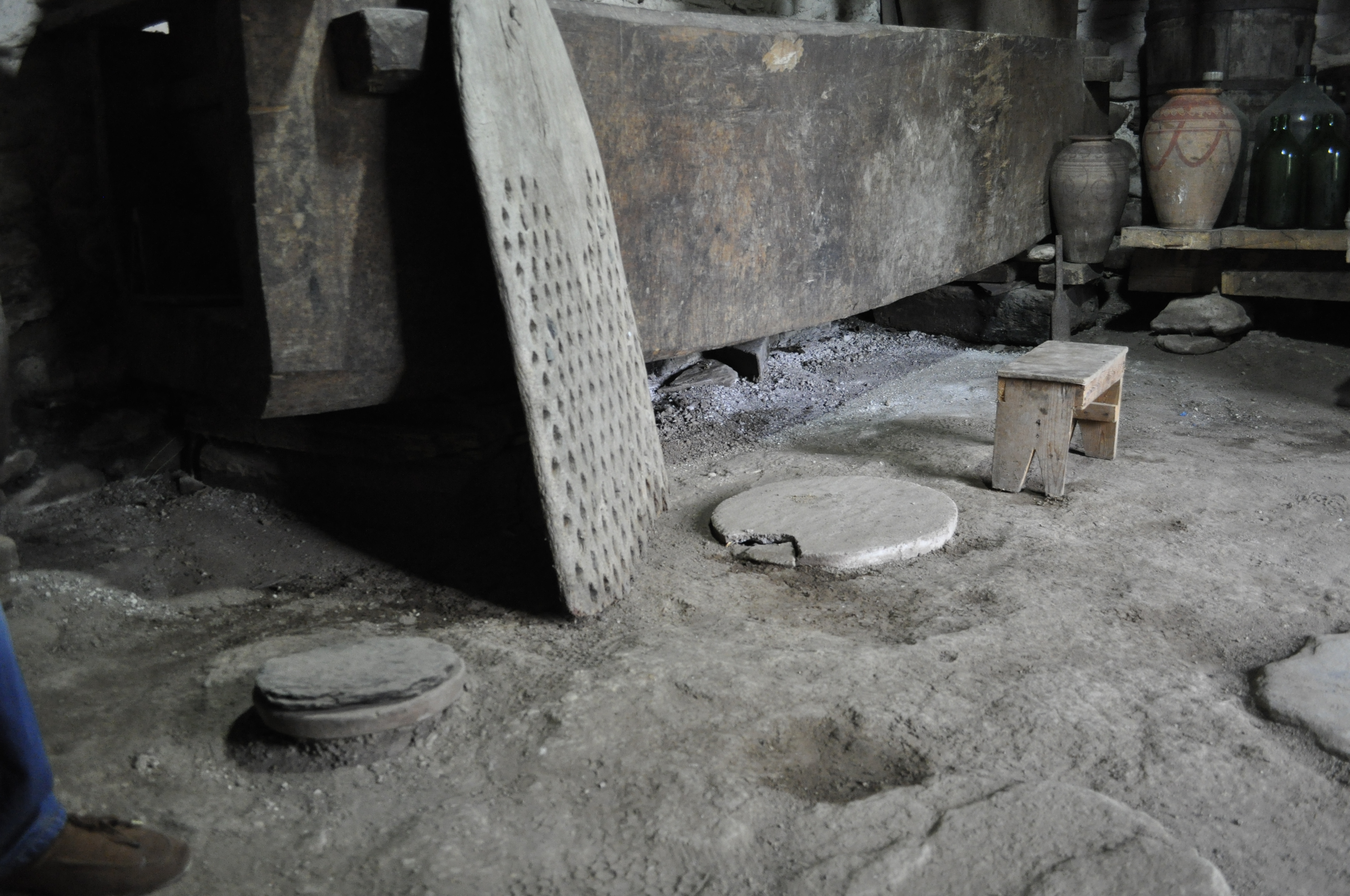 Cellar floor with details of jar (Kvevri) covers. The jars are used for winemaking. Detail of a tribulum for the threshing of cereals and a wine press, cellar (Marani), Kalaouri, Kakhétie region, Georgia, 18th century, October 2015