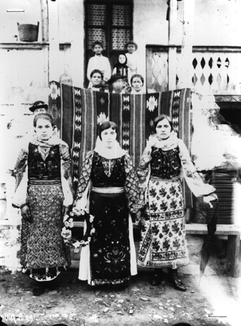 In the foreground, a group of three women, the one in the middle holding a shirt in her hand, Vâlcea area, Pitești region, 18 × 24 cm, early 20th century. Glass clichés collection